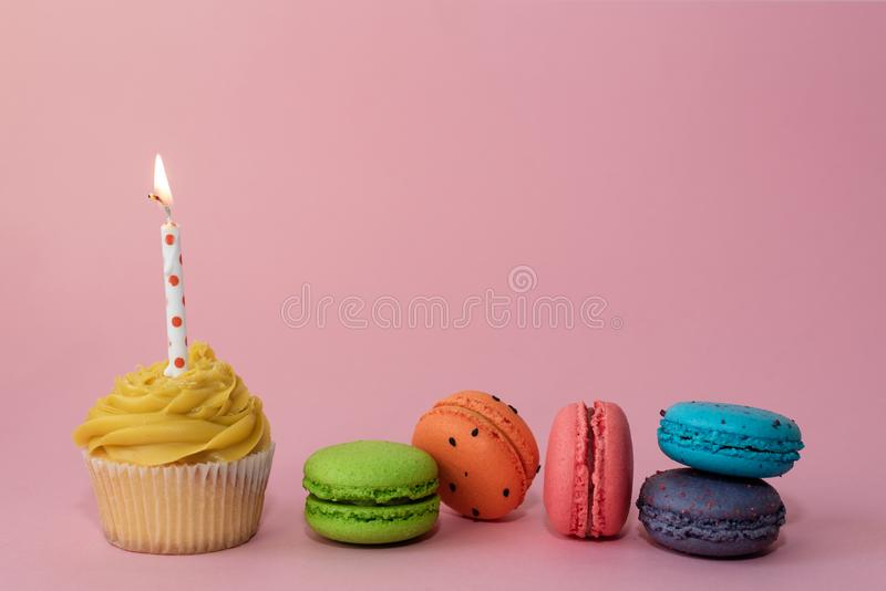 Yellow birthday cupcake with a candle and multi colored macaroons, on a pink background. Greeting card concept. Copy stock images