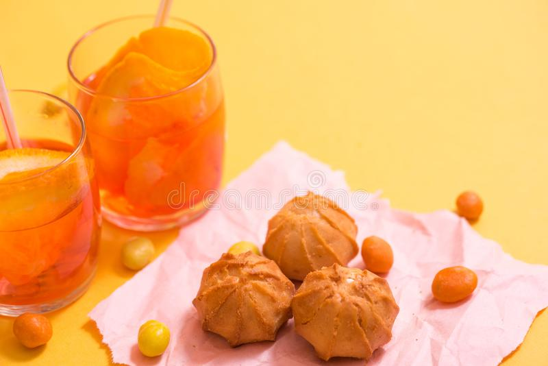 Yellow biscuits, orange drink with pieces of fruit in a glass cup on a yellow background. The concept of summer. Yellow biscuits, orange drink with pieces of royalty free stock photography
