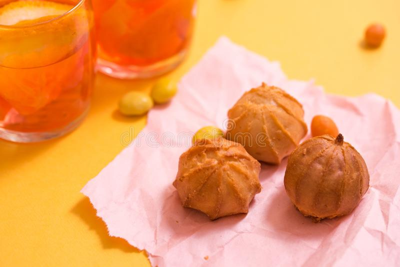 Yellow biscuits, orange drink with pieces of fruit in a glass cup on a yellow background. The concept of summer. Yellow biscuits, orange drink with pieces of stock photo