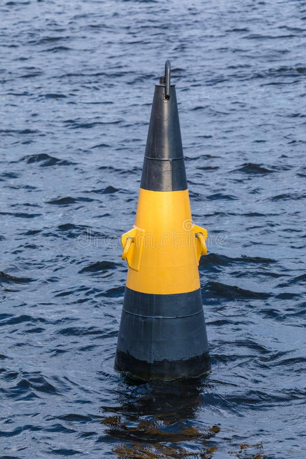 Yellow an black buoy on the waves of the river in the windy day. The warning sign near the shore of the port royalty free stock photography