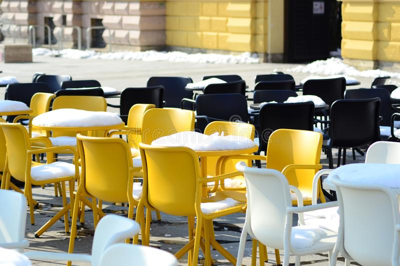 Yellow and black chairs covered in snow. Picture of yellow and black chairs covered in snow in winter stock photo