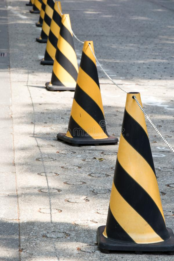 Yellow and black color traffic cone with the rope to guide royalty free stock image
