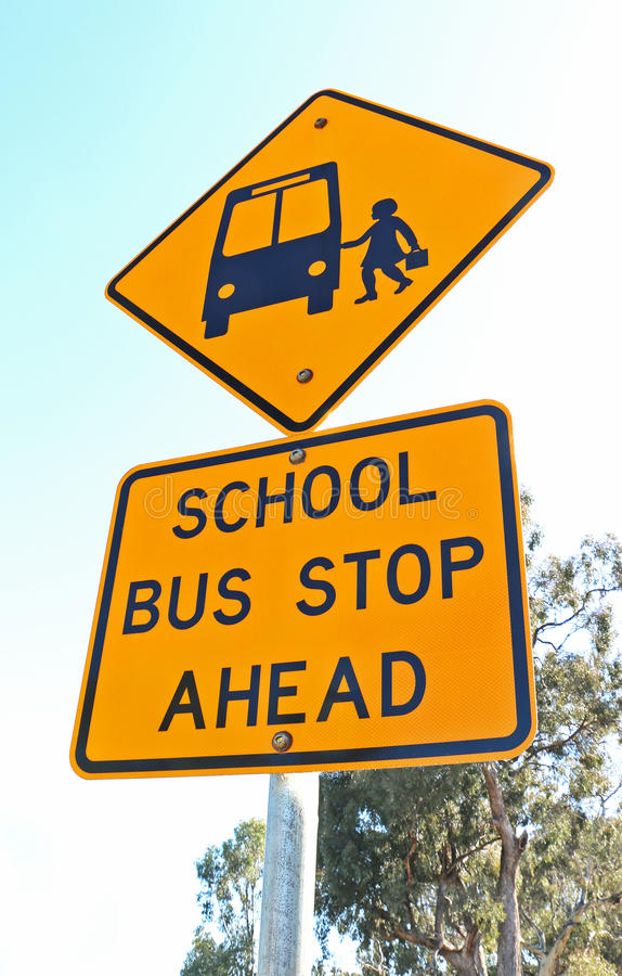 Yellow and black school bus stop ahead sign and blue sky royalty free stock image