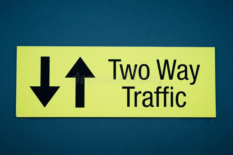 Yellow and black sign TWO WAY TRAFFIC with arrows on blue wall royalty free stock photos