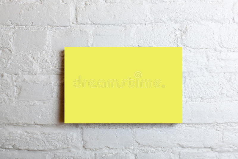Yellow blank poster in a white brick wall. Template Mock up for your content.  stock images