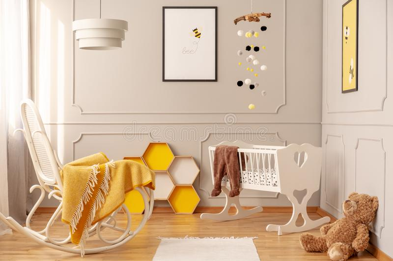 Yellow blanket on white wooden rocking chair in spacious baby bedroom with teddy bear and rug on the floor. Yellow blanket on white wooden rocking chair in stock image