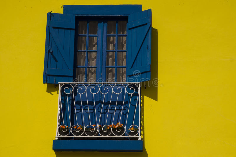 Yellow and blue Aveiro Portugal. Yellow facade, blue shutter, window,door and balcony with flowers Aveiro Portugal royalty free stock images
