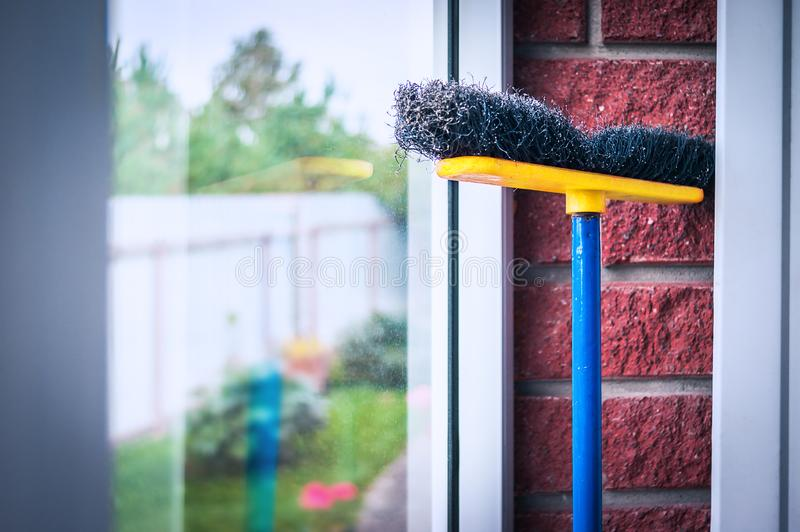 Yellow, Blue and Black Poly Push Broom Leaned Against the Glass and Red Brick Wall in the Mud Room. Keep Your Environment Clean. And Tidy Concept royalty free stock photography