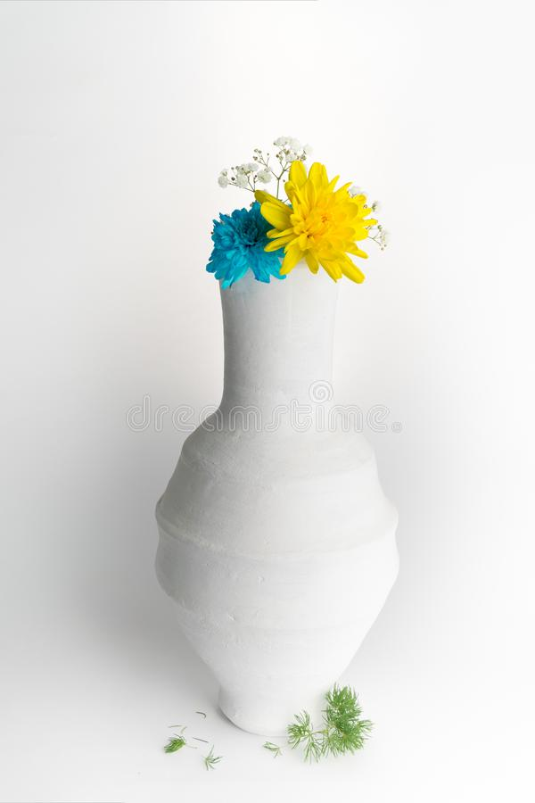 Yellow and blue flowers in white pottery vase on white background stock photo