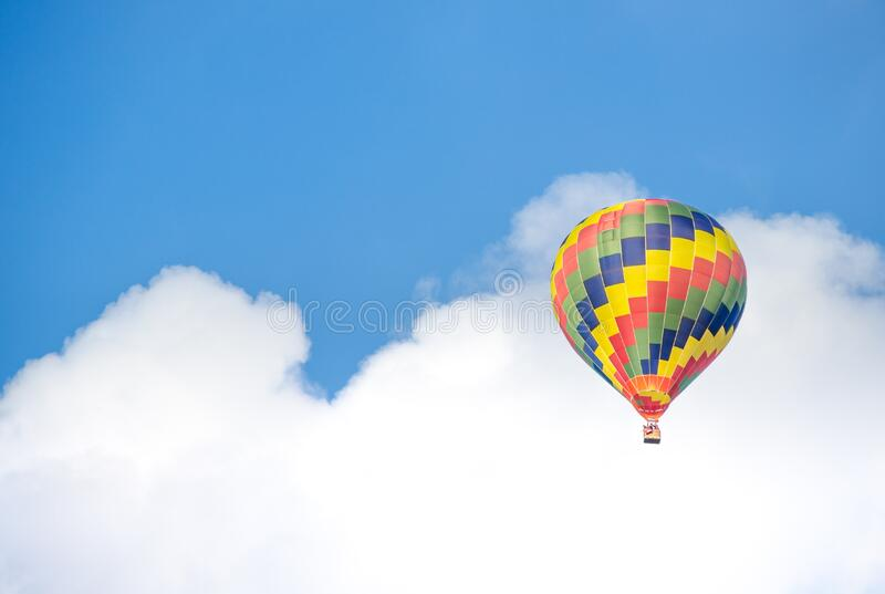 Yellow Blue and Green Hot Air Balloon Flying Near White Clouds stock photos