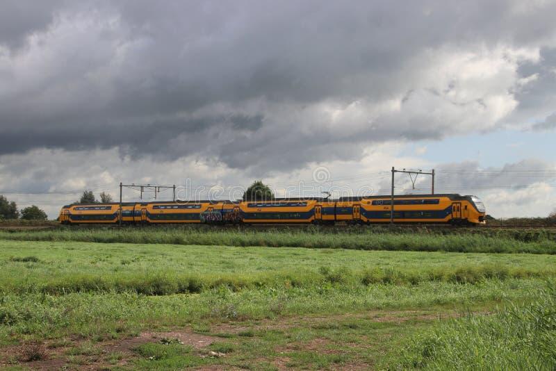 Yellow blue ibtercity doubl3 decker train heading to Rotterdam from Gouda stock photos