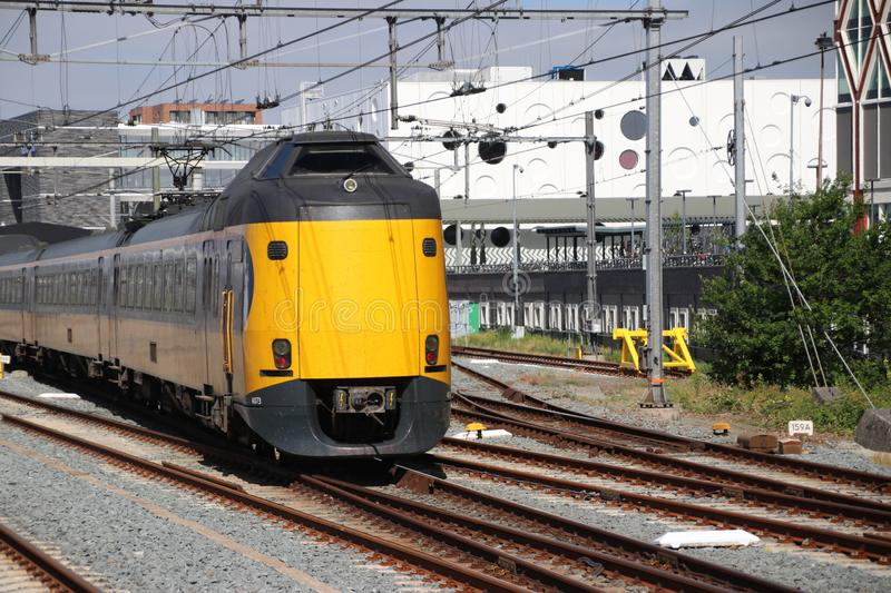 Yellow blue intercity train at the station of the city Gouda heading to Utrecht royalty free stock photography