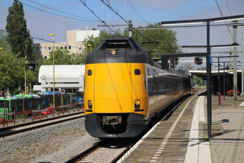 Yellow blue intercity train at the station of the city Gouda heading to Utrecht stock photography