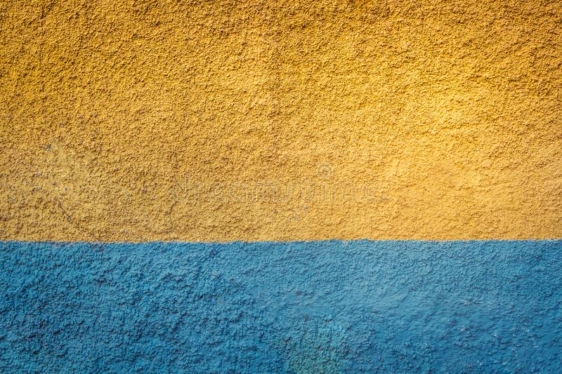 Yellow and blue painted grunge wall background royalty free stock photo
