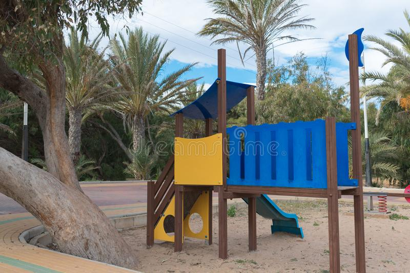 Yellow and blue park play equipment for childrens with palmtrees background royalty free stock photo