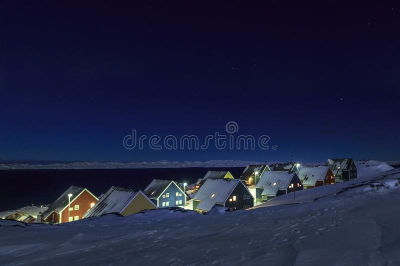Yellow, blue, red and green inuit houses covered in snow at the fjord under the starlight sky, Nuuk city, Greenland. Architecture arctic bay buildings capital stock images
