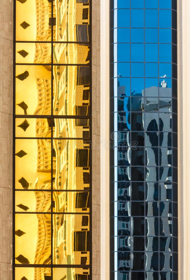 Yellow and blue reflections on facade glass of high rise building royalty free stock photography
