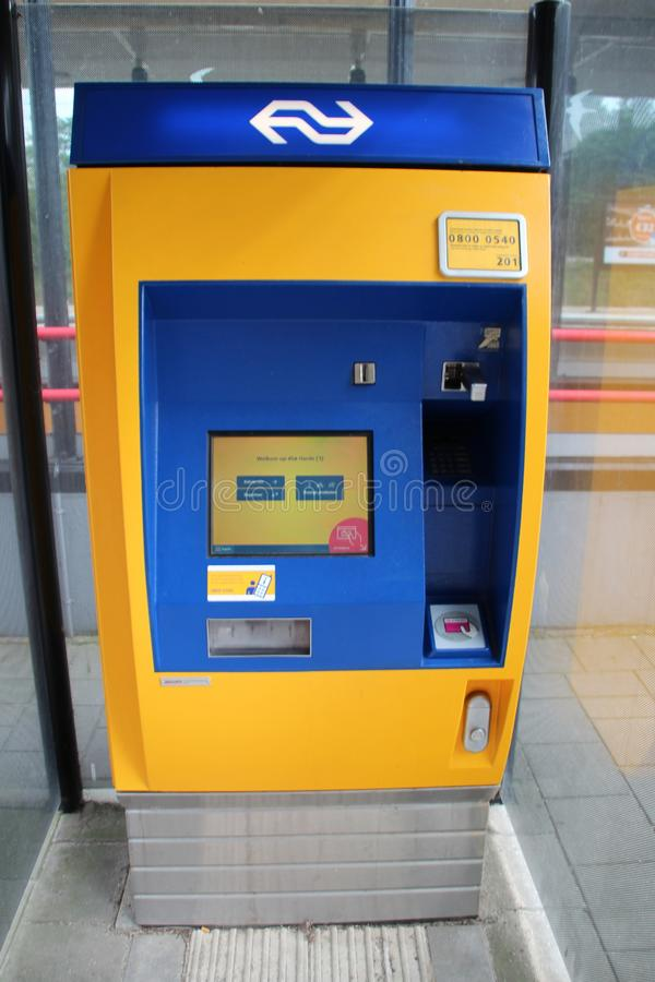 Yellow blue ticket machine of the dutch railways on a station platform stock images