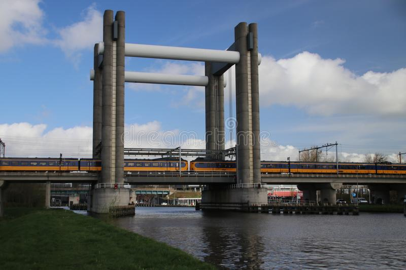 Yellow blue train type koploper of dutch Railways NS on the train bridge of Gouda in the Netherlands royalty free stock images