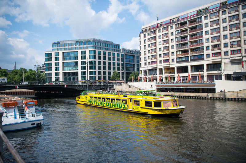 Yellow boat with tourists on river water in city stock images