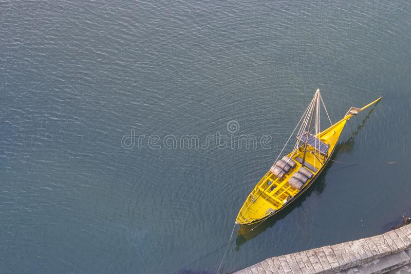 Yellow boat with wine barrels view from above. Boat on water top aerial view. Yellow wooden boat in Porto, Portugal. Vintage kayak on river Douro, Portugal royalty free stock photography
