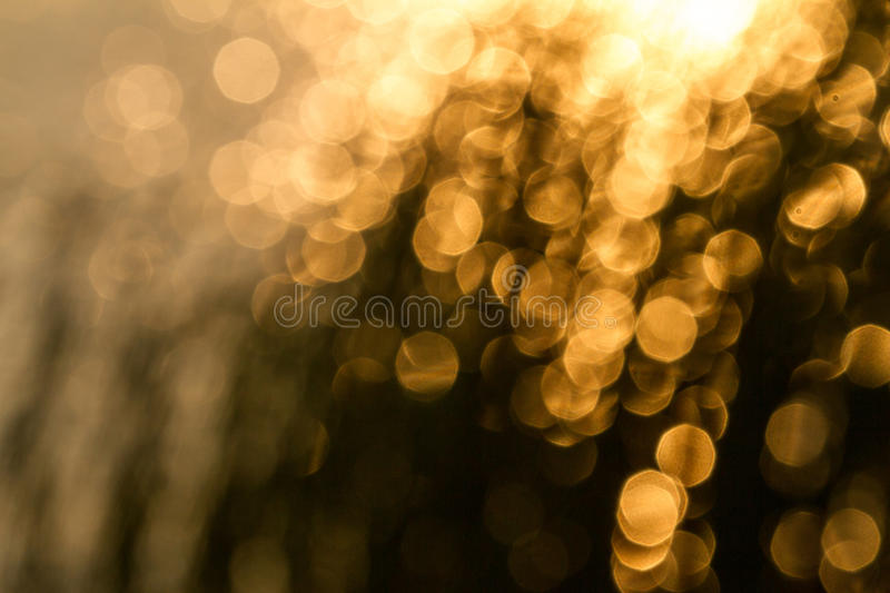 Yellow bokeh. On dark brown background