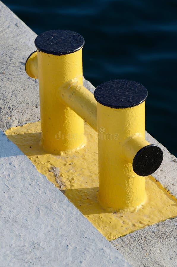 Yellow bollard pier - device for yacht mooring in marina royalty free stock photos