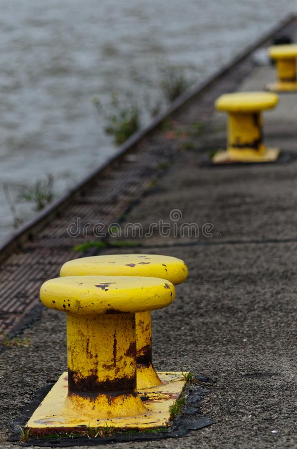 Yellow bollards on the quay. Near to so-called Treppenviertel lit. stairs quarter in Hamburg Blankenese, Germany royalty free stock photography