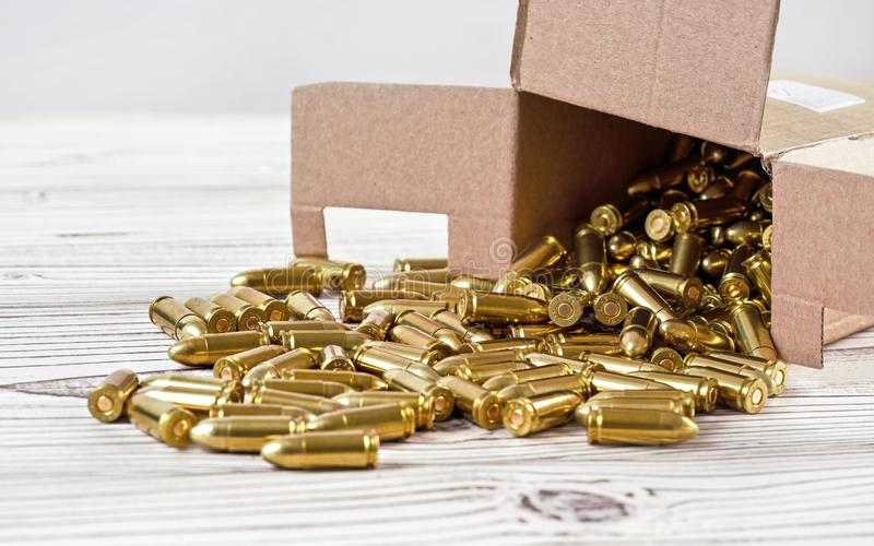 Yellow brass gun ammo spilled from paper carton box on white boar desk - close up stock photo