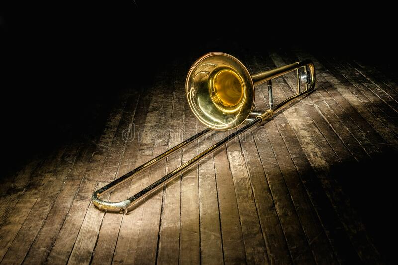 Golden brass instrument trombone lies on a dark brown wooden stage in the rays of light royalty free stock photography