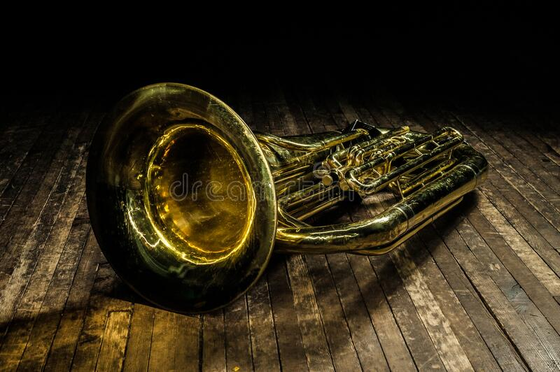 Golden brass wind instrument euphonium lies on a brown wooden stage in the light of a spotlight royalty free stock photos