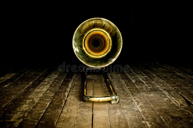 Yellow brass instrument trombone lies on the wooden floor of the stage. front view on the bell stock photography