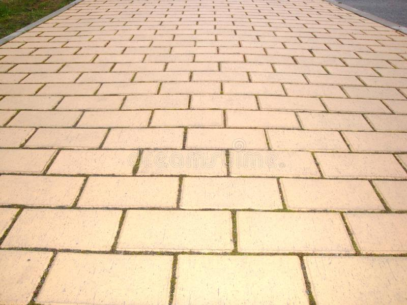 Road covered with yellow pavement tiles. Yellow brick road. Abstract background. Urban design. Yellow tile walkway royalty free stock photography