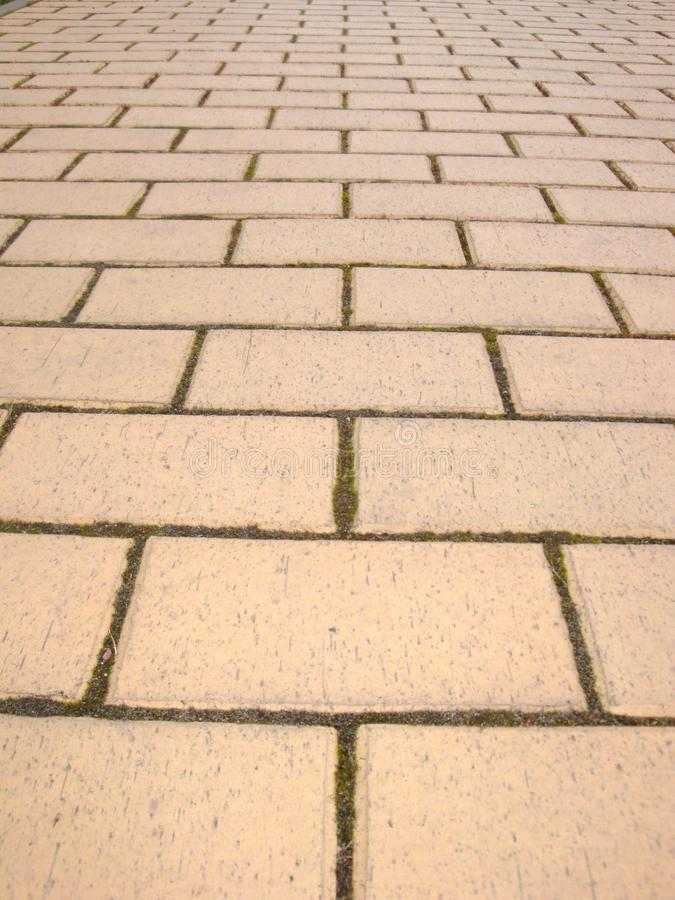 Road covered with yellow pavement tiles. Yellow brick road. Abstract background. Urban design. Yellow tile walkway stock photos