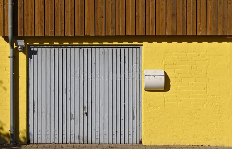 Yellow brick wall with garage door, mail box, downspout and wooden paneling on the second floor stock photography
