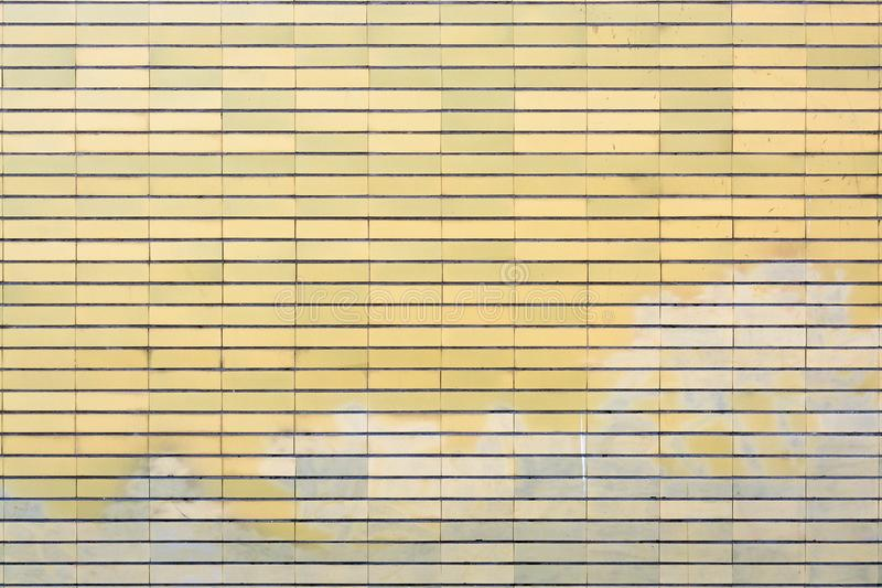 Yellow brick wall surface. Old yellow tiled brick surface with washed out graffiti on the lower part stock photo
