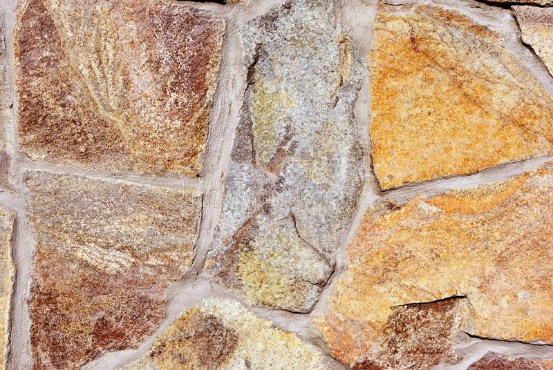 Yellow-brown stones wall surface close up detail. Grunge horizontal background royalty free stock photography