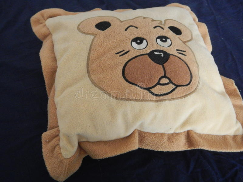 Yellow and brown teddy bear pillow stock image