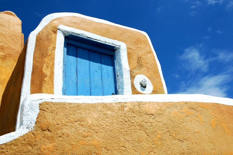 Yellow building with blue door in Oia, Santorini, Greece royalty free stock photo