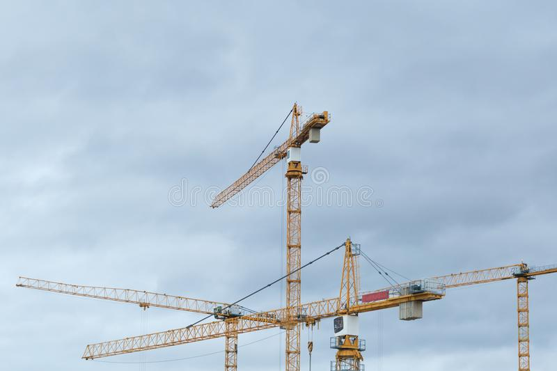Building constraction cranes against the grey sky. Yellow building constraction cranes against the grey sky royalty free stock photography