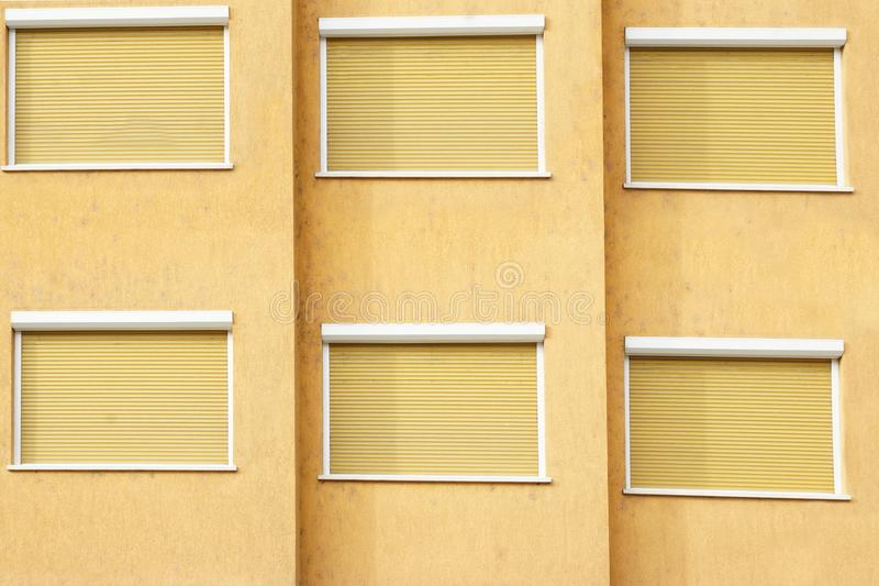 Yellow Building Facade with Six Closed Windows Shutters. Background with Space for Text or Image royalty free stock photos