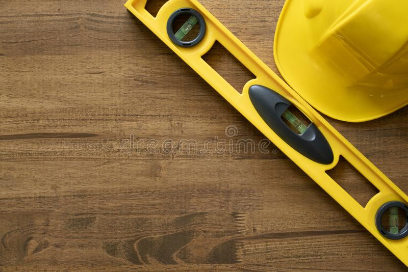 Yellow building level and yellow helmet on the old wood table. Engineering work tool concept stock image