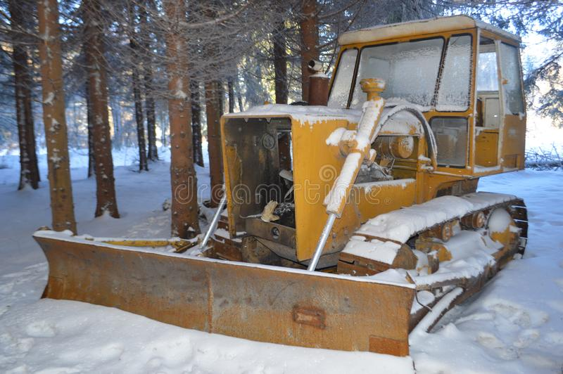 Bulldozer covered with snow in forest royalty free stock photo