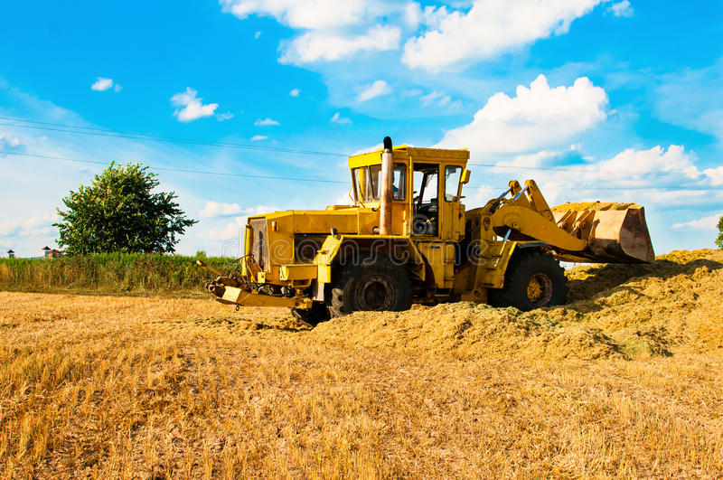 Yellow bulldozer in a field at harvest. On a Sunny day royalty free stock photography