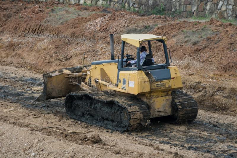 Yellow Bulldozer scooping dirt at a construction site royalty free stock photos