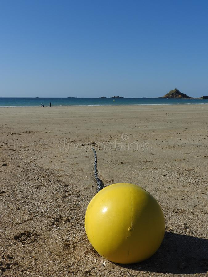 A yellow buoy on the beach. Yellow buoy on the beach, sea and blue sky in the background royalty free stock image