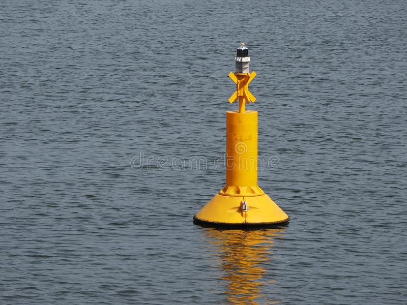 Yellow buoy floating in the sea. Waves royalty free stock photo