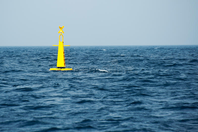 Yellow buoy on sea. Floating yellow buoy on blue sea royalty free stock photography
