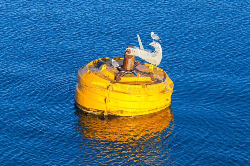 Yellow buoy with seagulls floats on water. Yellow mooring buoy with seagulls floating on blue sea water royalty free stock photography
