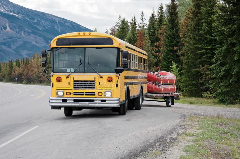 Yellow bus carries two red boats royalty free stock image